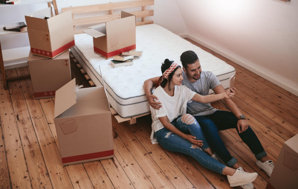 tenant communication header image: young couple sitting on floor of room next to moving boxes videochatting on the phone