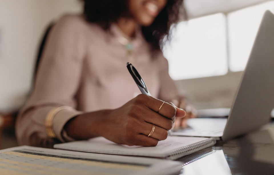 how to be a good landlord : woman writing notes while sitting at her desk