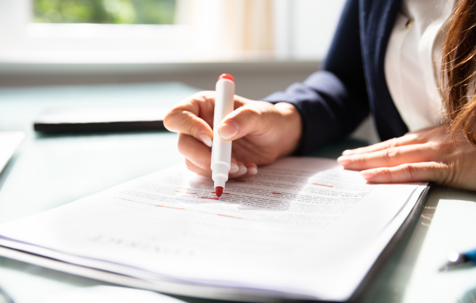 state lease laws: woman's hand holding highlighter over a stack of papers