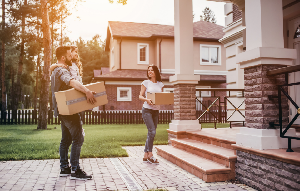 screening tenants without a credit check: image of a couple moving into house carrying boxes