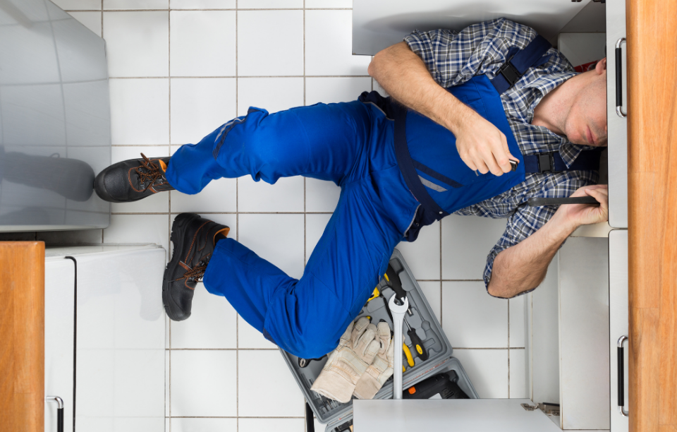 maintenance with rentredi latchel: man wearing blue overalls fixing pipe under sink