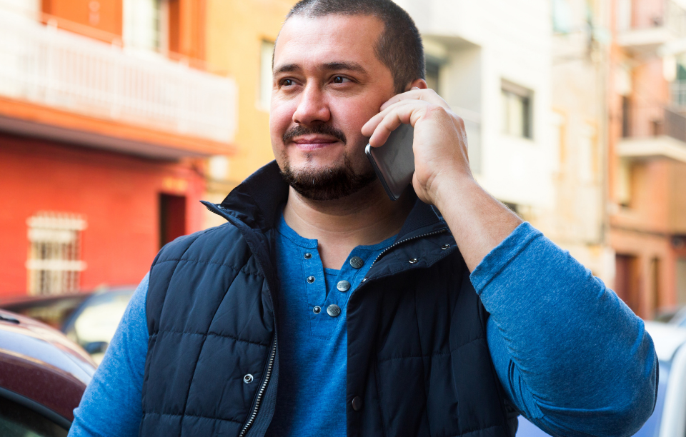landlord reference image: man wearing blue shirt and vest talking on phone