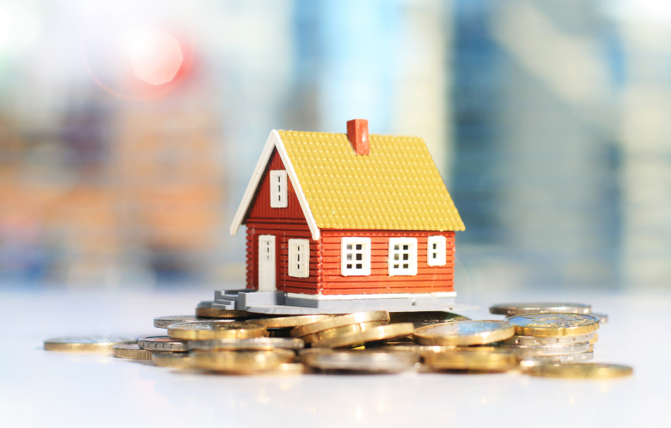 financial freedom with real estate header image: picture of a tiny house sitting on top a pile of coins