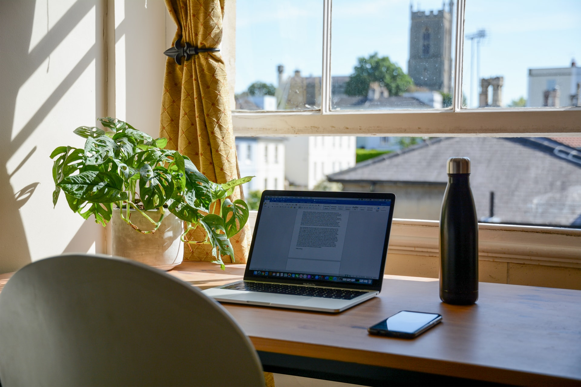 working from home set up: desk, laptop, plan, water bottle, phone