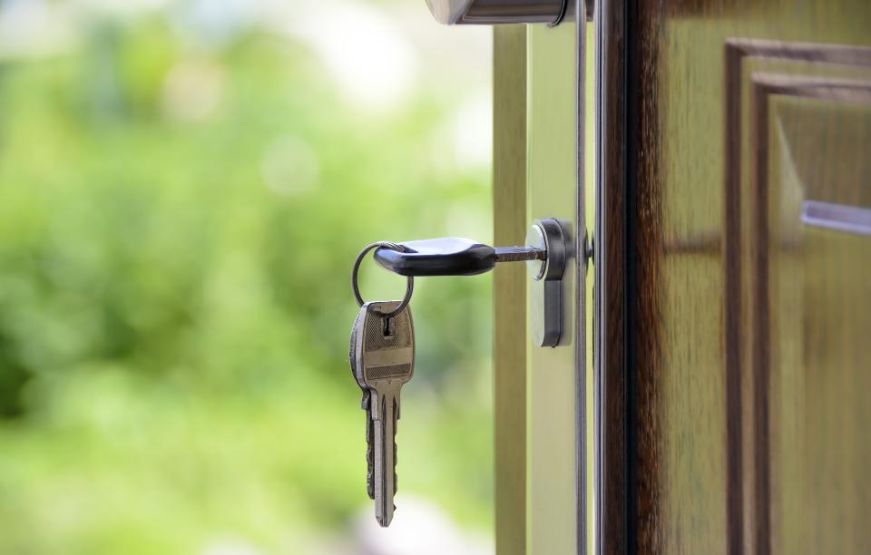 set of silver keys in wooden door for home loan