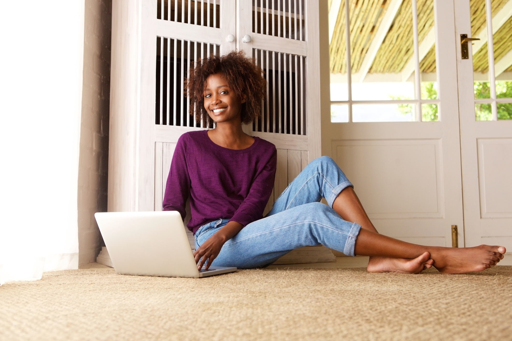 rentredi vs appfolio hero image: Smiling black woman sitting with laptop at home