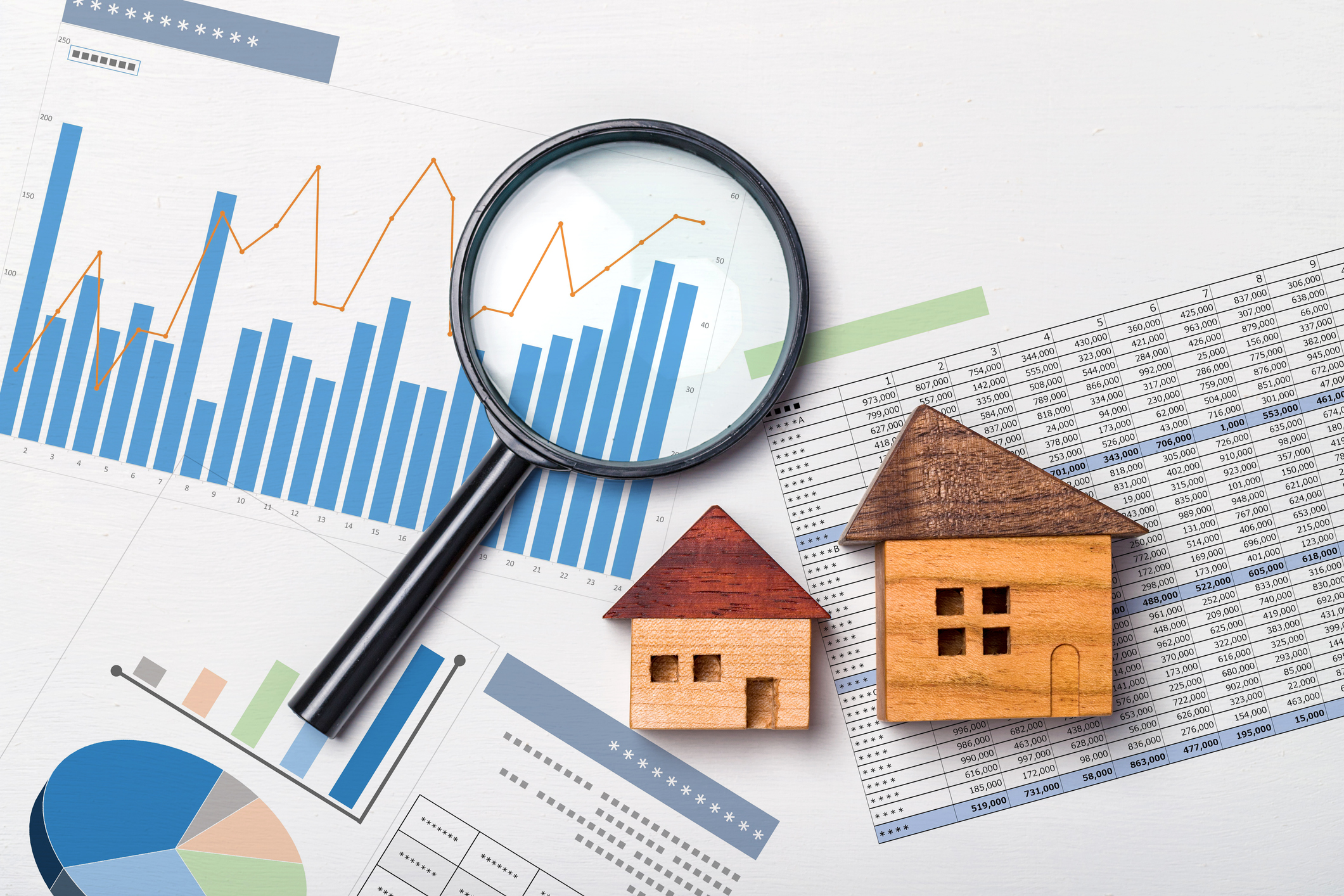 image of charts, magnifying glass, and mini wood houses to represent real estate market metrics