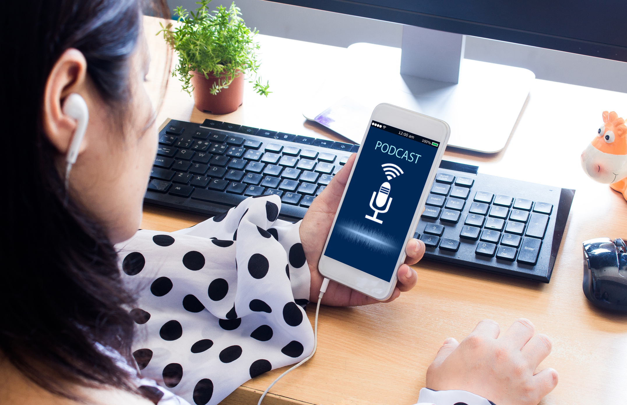 header image for real estate podcast: over-the-shoulder shot of woman holding phone listening to a podcast