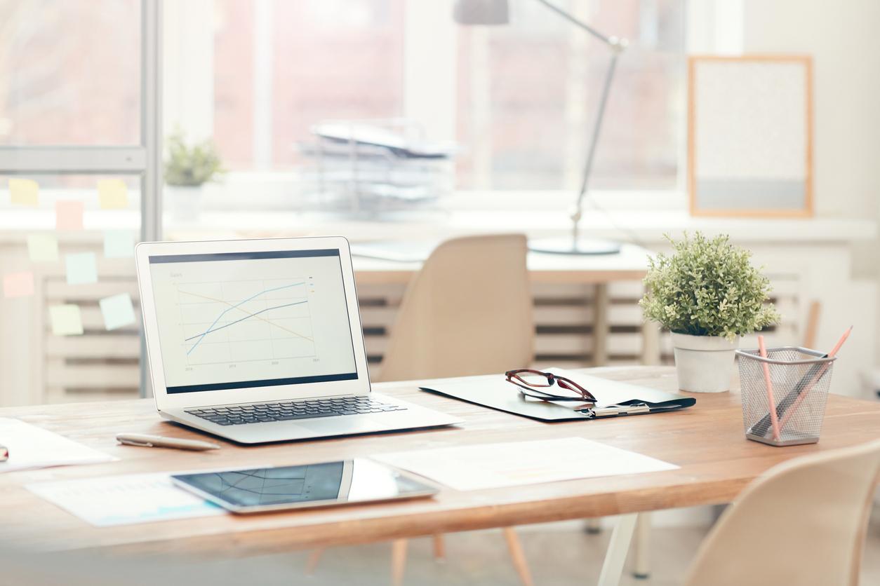 prescreening tenants hero image: laptop sitting open on a desk in a brightly lit room