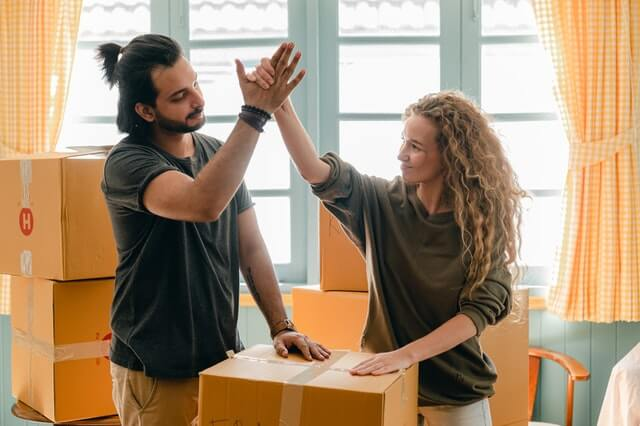 hero image for move in/move out inspection: couple high fiving while packing boxes to move