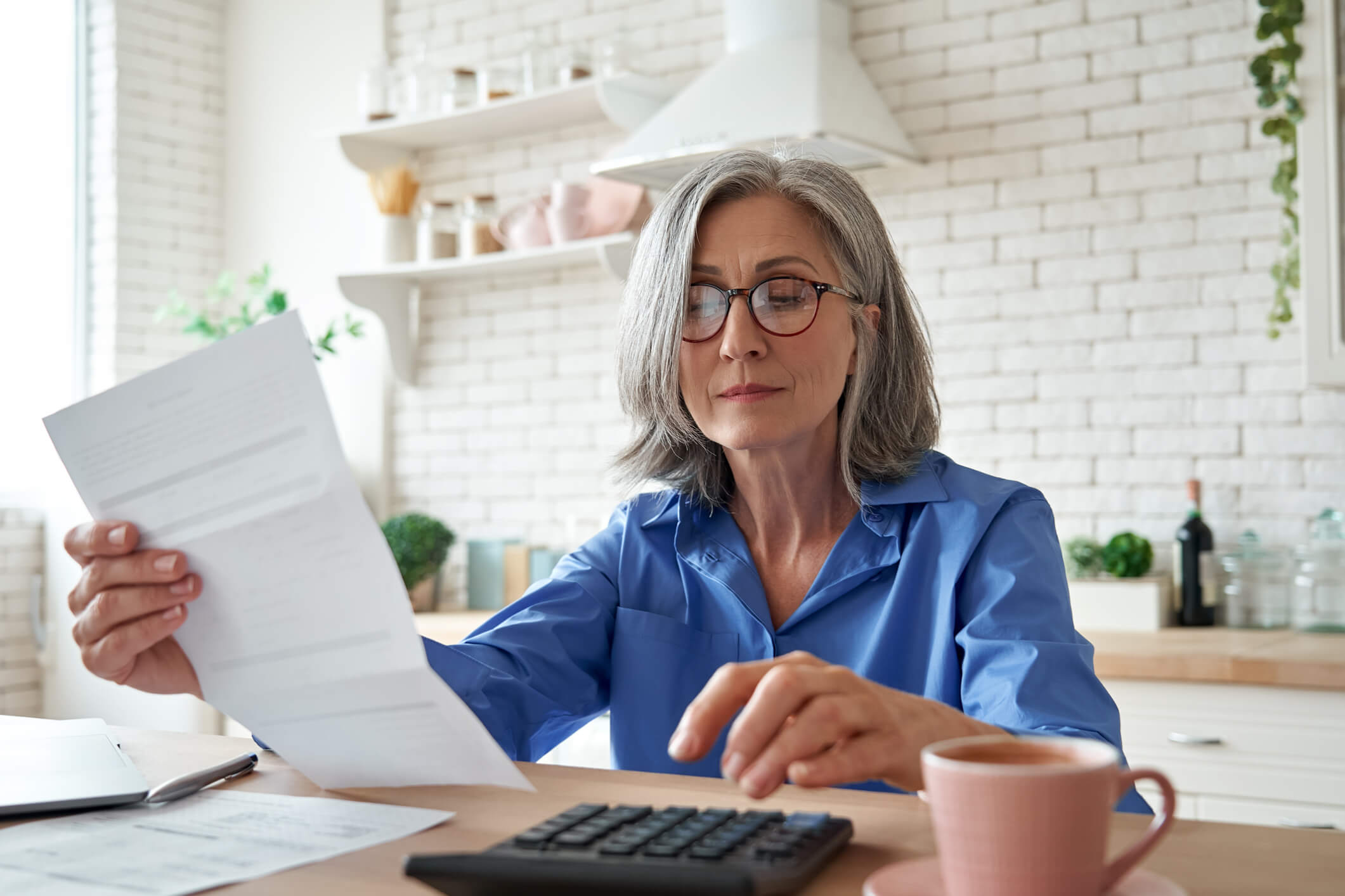accounting software for landlords hero image: woman with grey hair and glasses sitting at kitchen table calculating payments