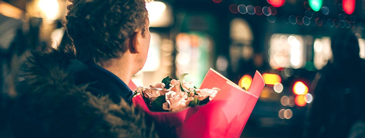 Mann bereitet sich auf den Valentinsgstag vor und hat Blumen für seine Traumfrau in der Hand.