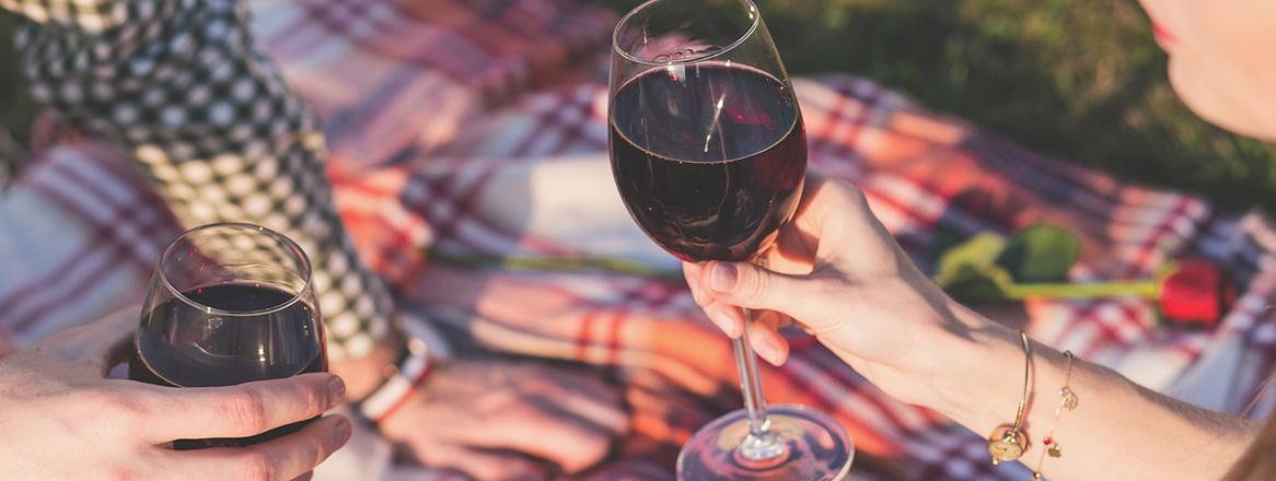 Date Ideen sollen kreativ sein. Hier ist ein Paar zu sehen, das zusammen ein Picknick macht und Wein trinkt.