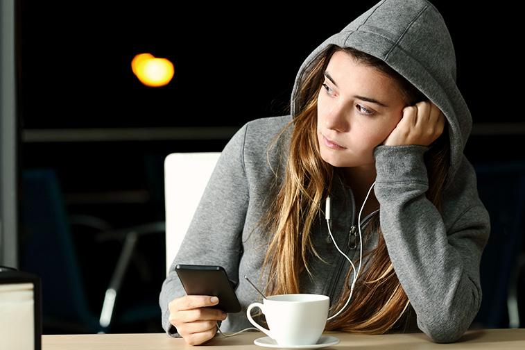 Frau sitzt traurig im Café und sieht aus dem Fenster