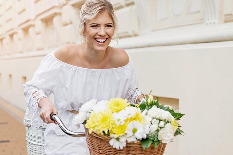 Glückliche Frau sitzt auf einem Fahrrad mit Blumenkorb und fährt.