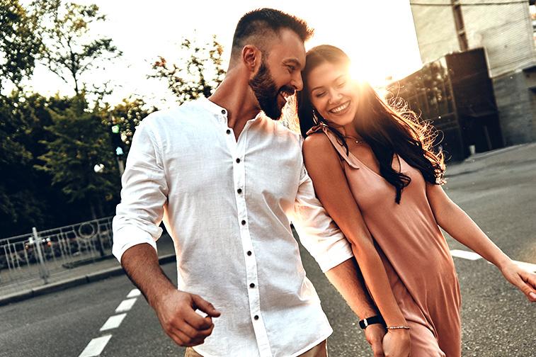 Mann und Frau gehen händchen haltend über die Straße