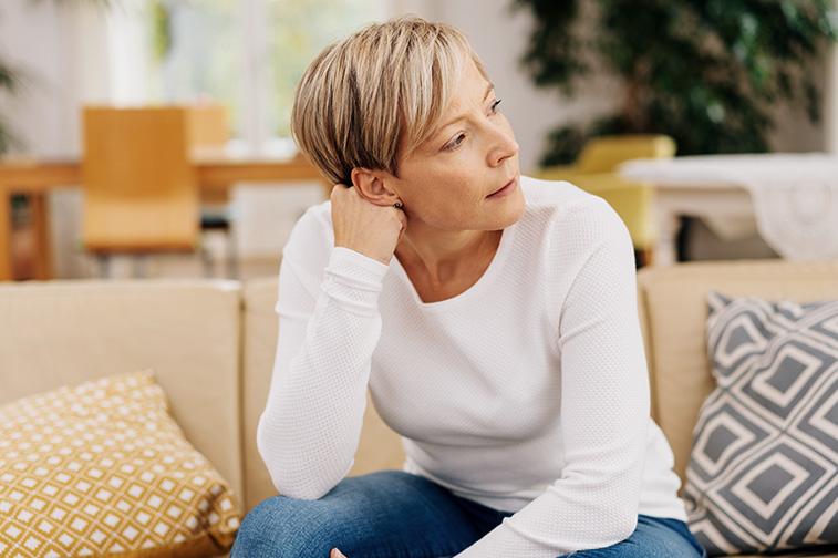 Frau sitzt auf dem Sofa und sieht nachdenklich weg