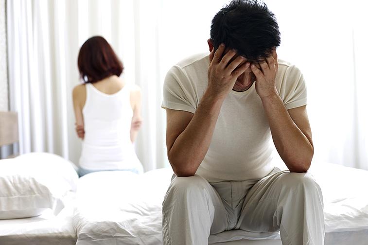 Mann sitzt auf dem Bett, die Hände vor dem Gesicht und wendet sich von der Frau ab