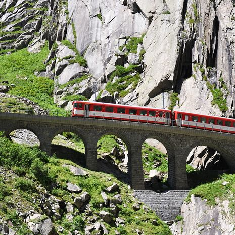 Alpine express passing bridge at St. Gotthard Pass, Switzerland