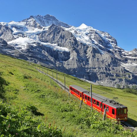 Electric red tourist train coming down from the Jungfraujoch station in Kleine Scheidegg, Bernese Oberland