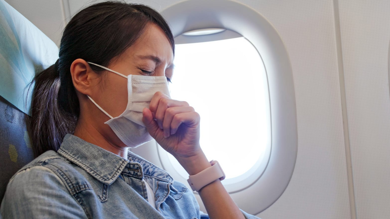 photo of woman sneezing with mask on face airplane thanksgiving will i get sick flu influenza shot vaccine flight holiday travel immunity immune system robin thompson