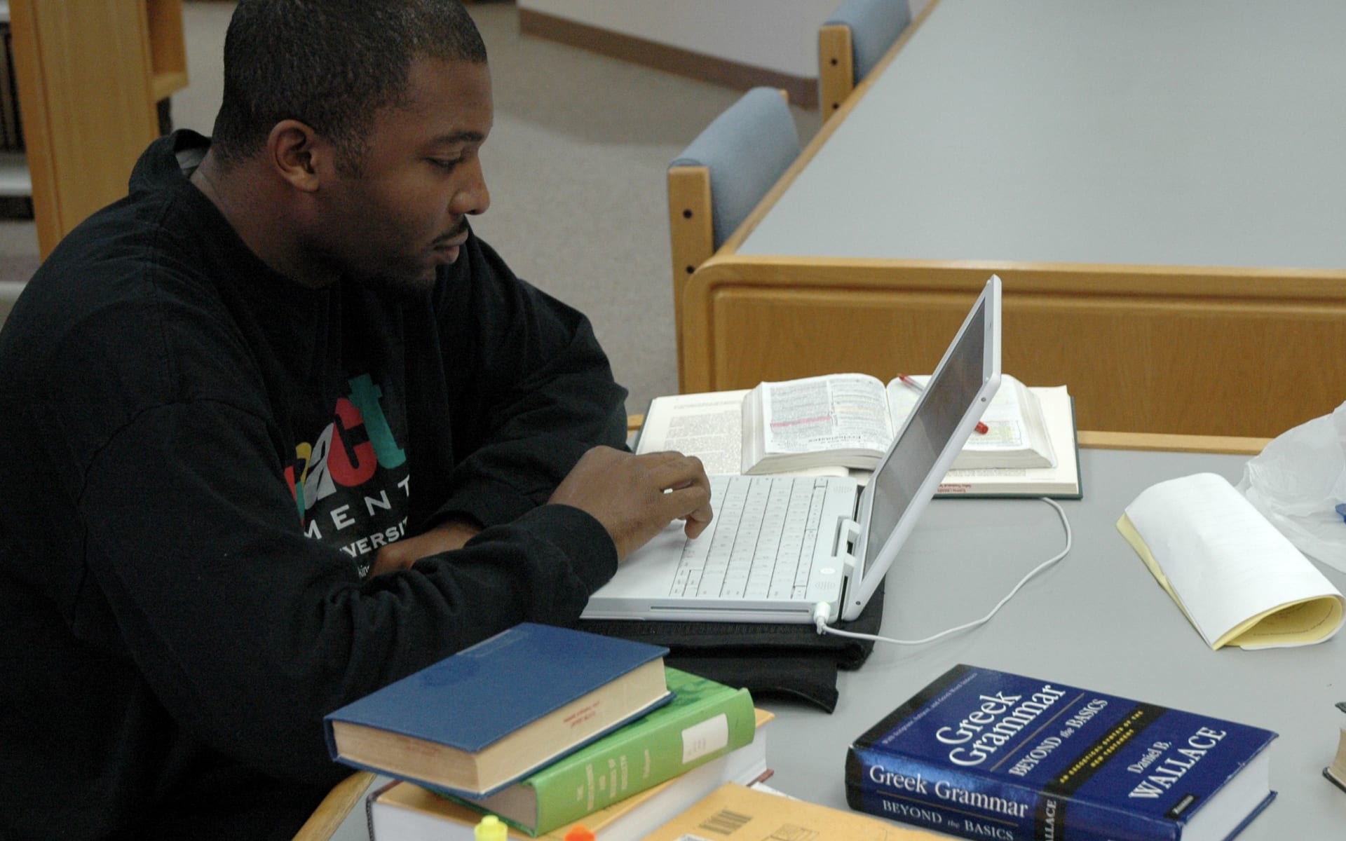 man studying at a table in the library with his laptop
