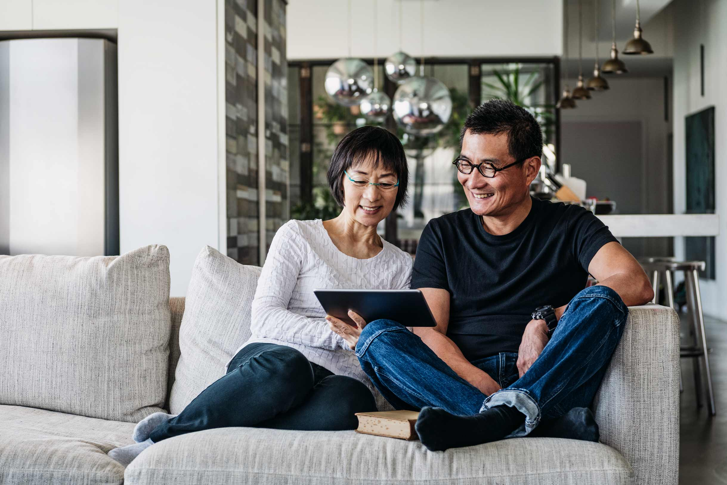 Chinese couple sitting on a couch reading a book