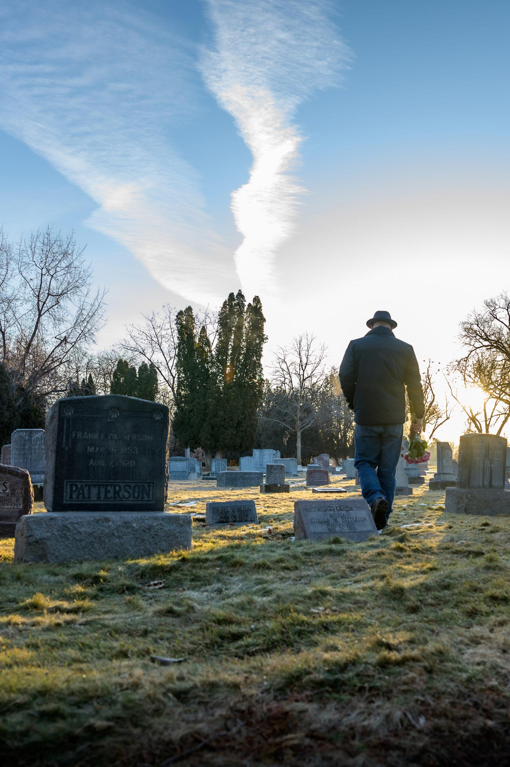 Lone figure of a man walking through a cemetery.