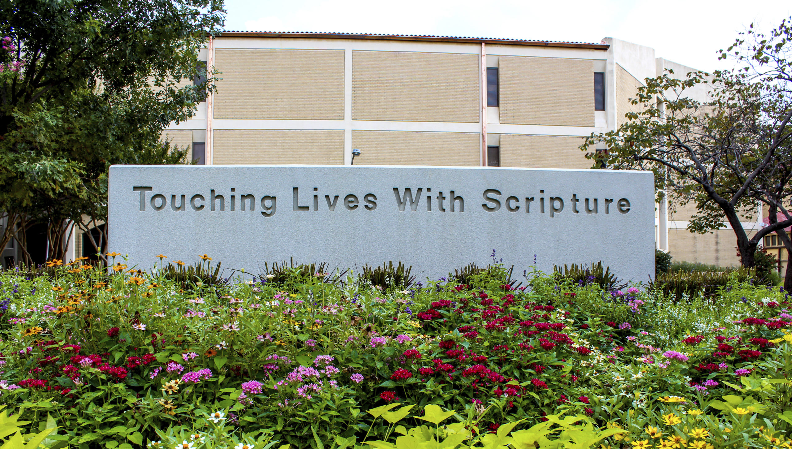sign on campus that reads touching lives with scripture