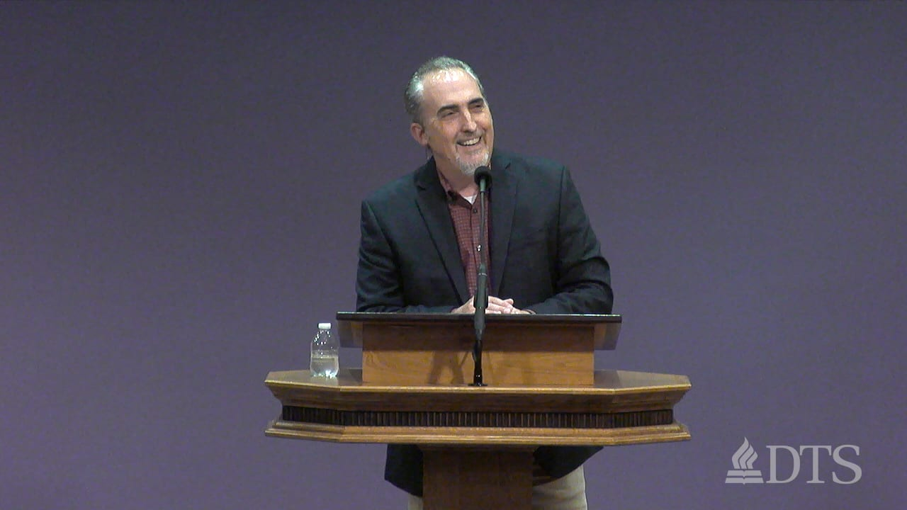 Dr. Mark Yarbrough standing at a podium speaking at DTS Chapel