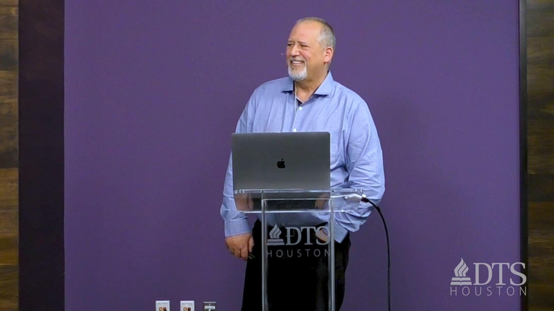 Dr. Glenn Kreider standing at podium speaking at DTS Chapel