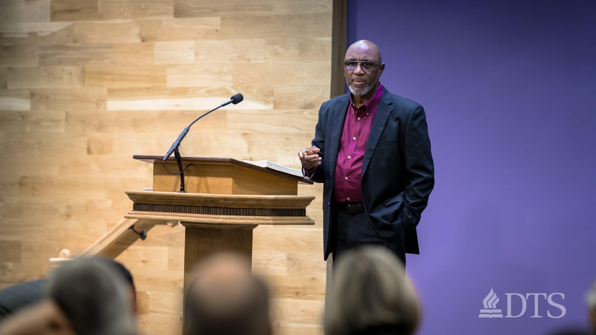 man standing next to podium speaking at DTS Chapel