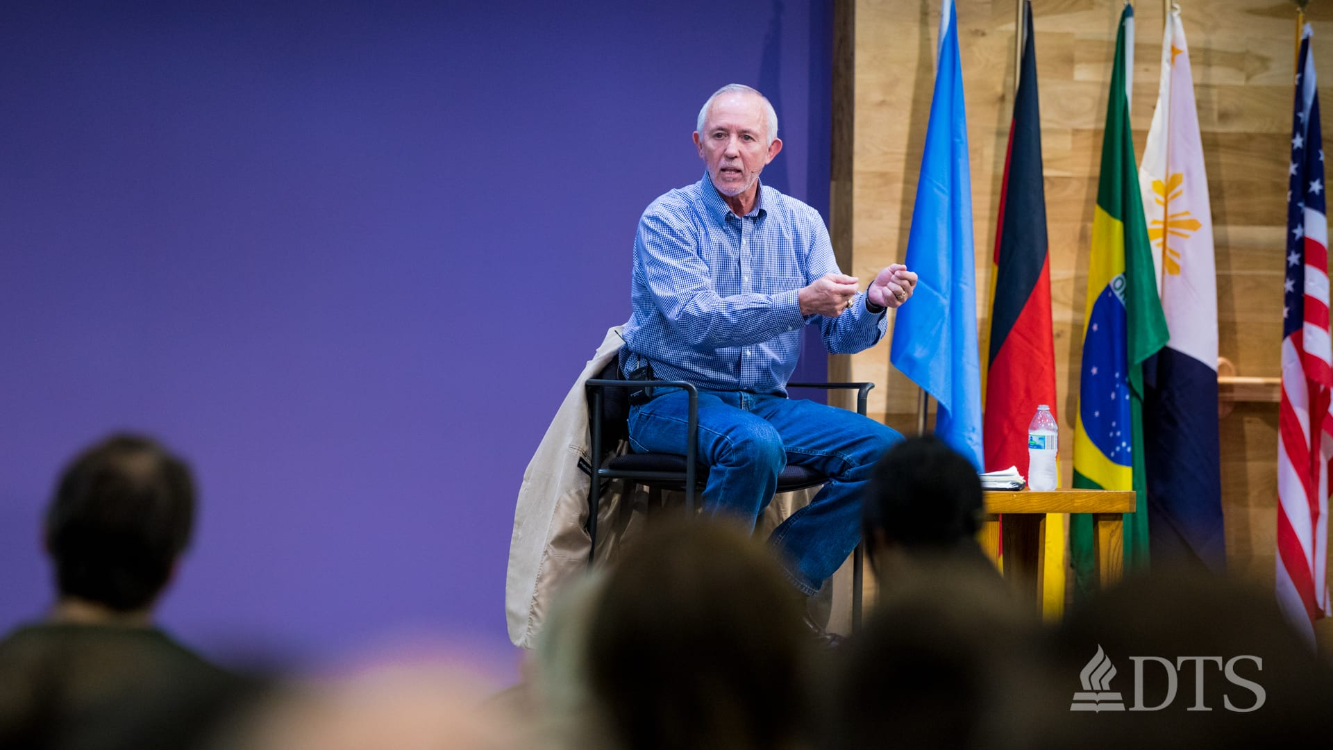 man seated on stage speaking at DTS WEC Week
