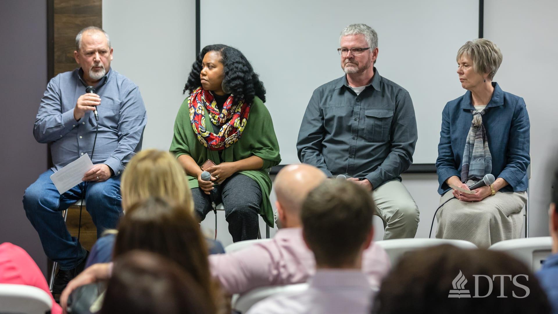 Dr. Glenn Kreider seated with men and women speaking as