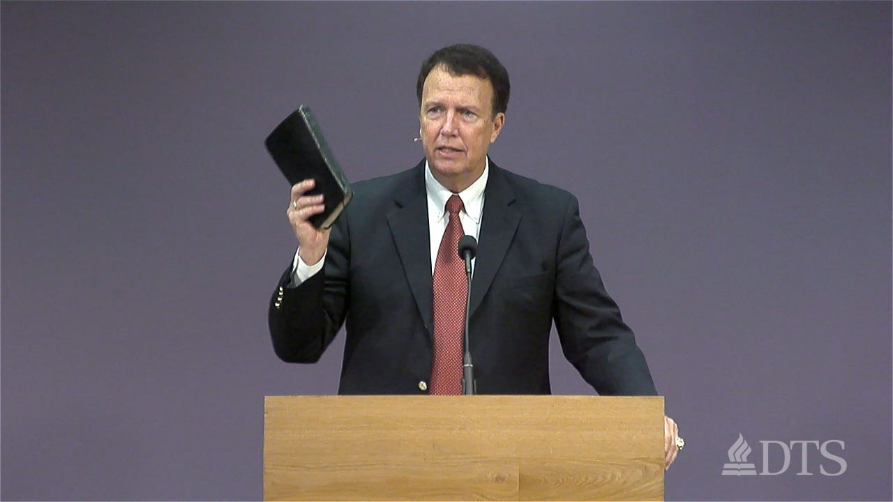man standing at podium holding his Bible in the air while speaking at DTS Chapel