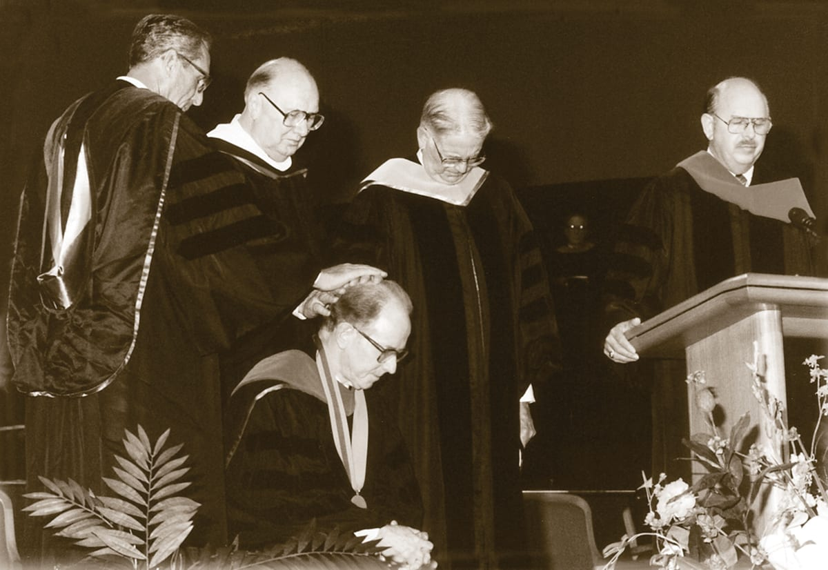 Dr. Campbell kneeling while prayed for at DTS inauguration