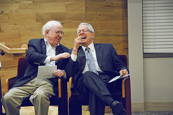 Dr. Campbell seated next to Dr. Swindoll while laughing