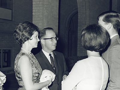 Dr. Campbell with his wife talking to a man and woman on DTs campus