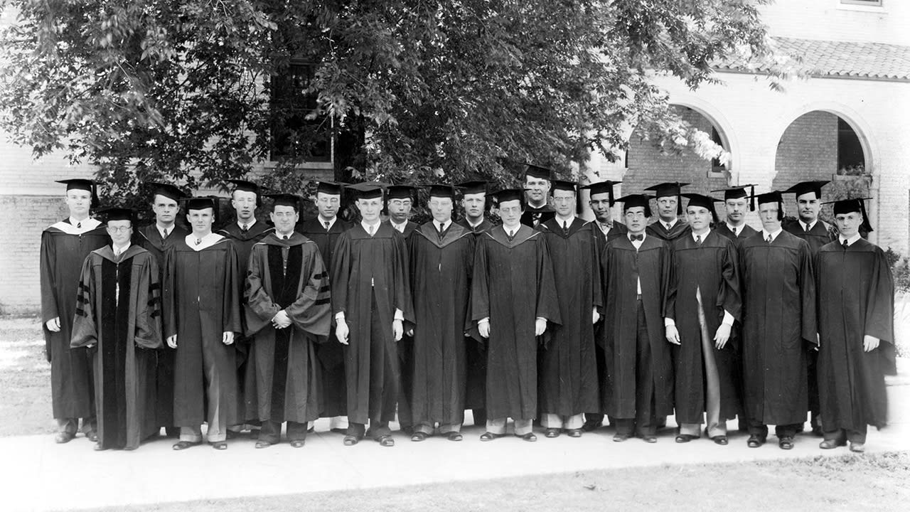 Group of male graduates in caps and gowns on DTS campus