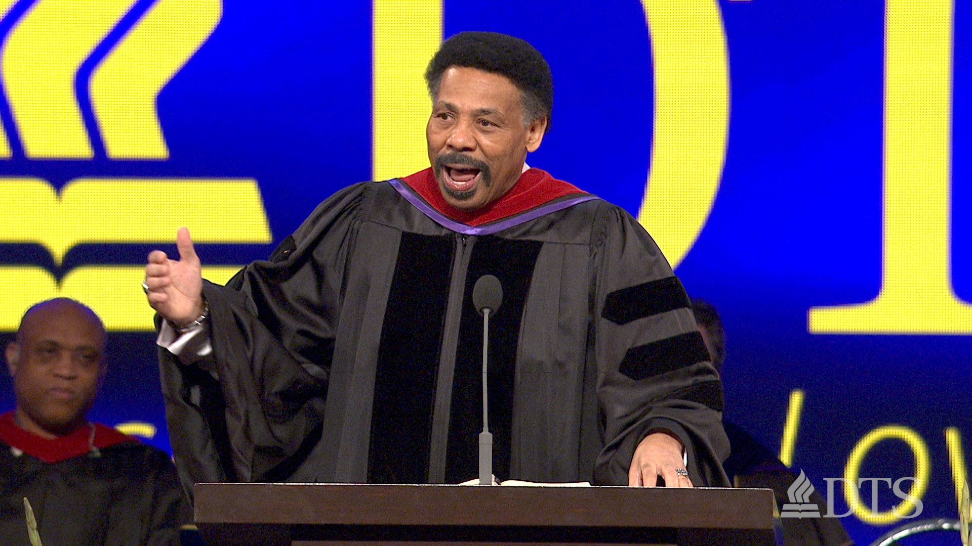 Dr. Tony Evans standing at a podium speaking during DTS commencement