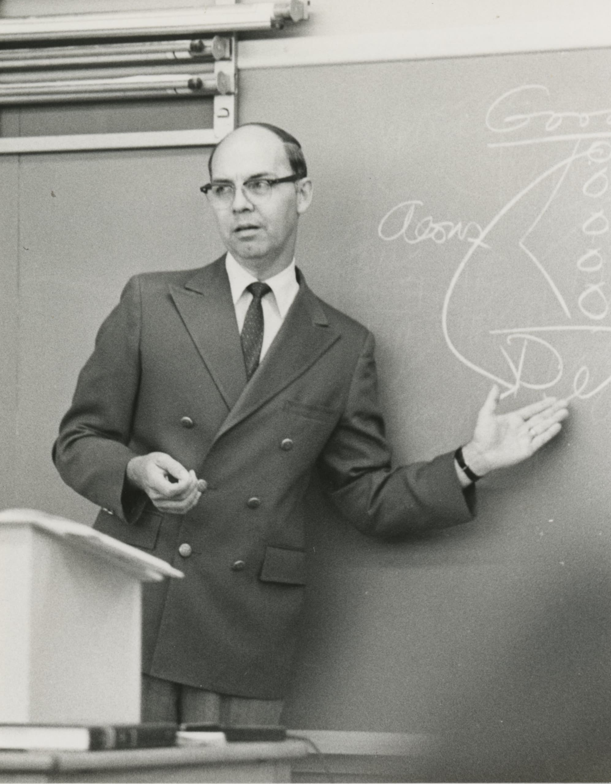 Dr. Lightner pointing to wording written on a chalkboard