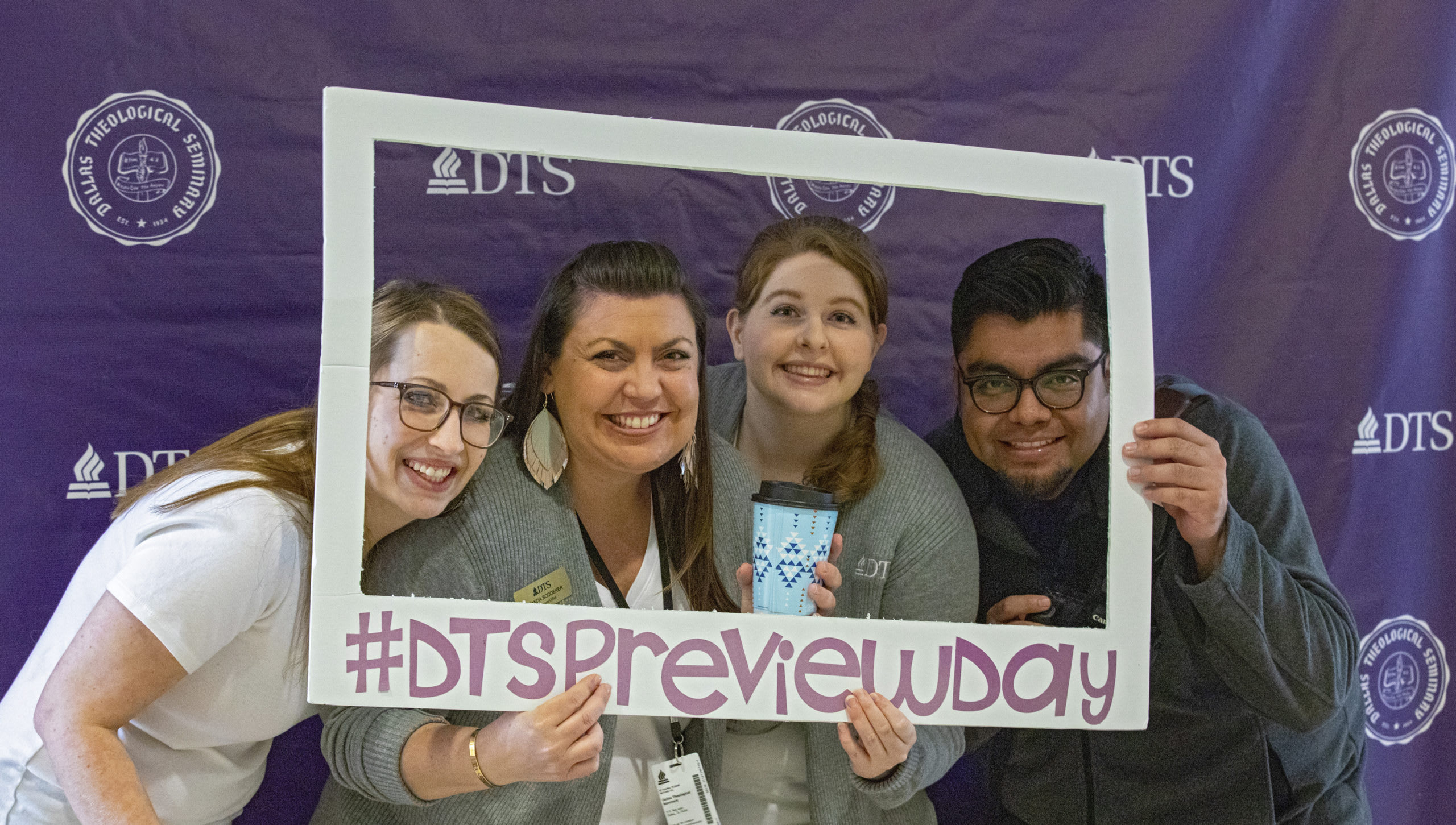 four people hold a sign that says DTS preview day