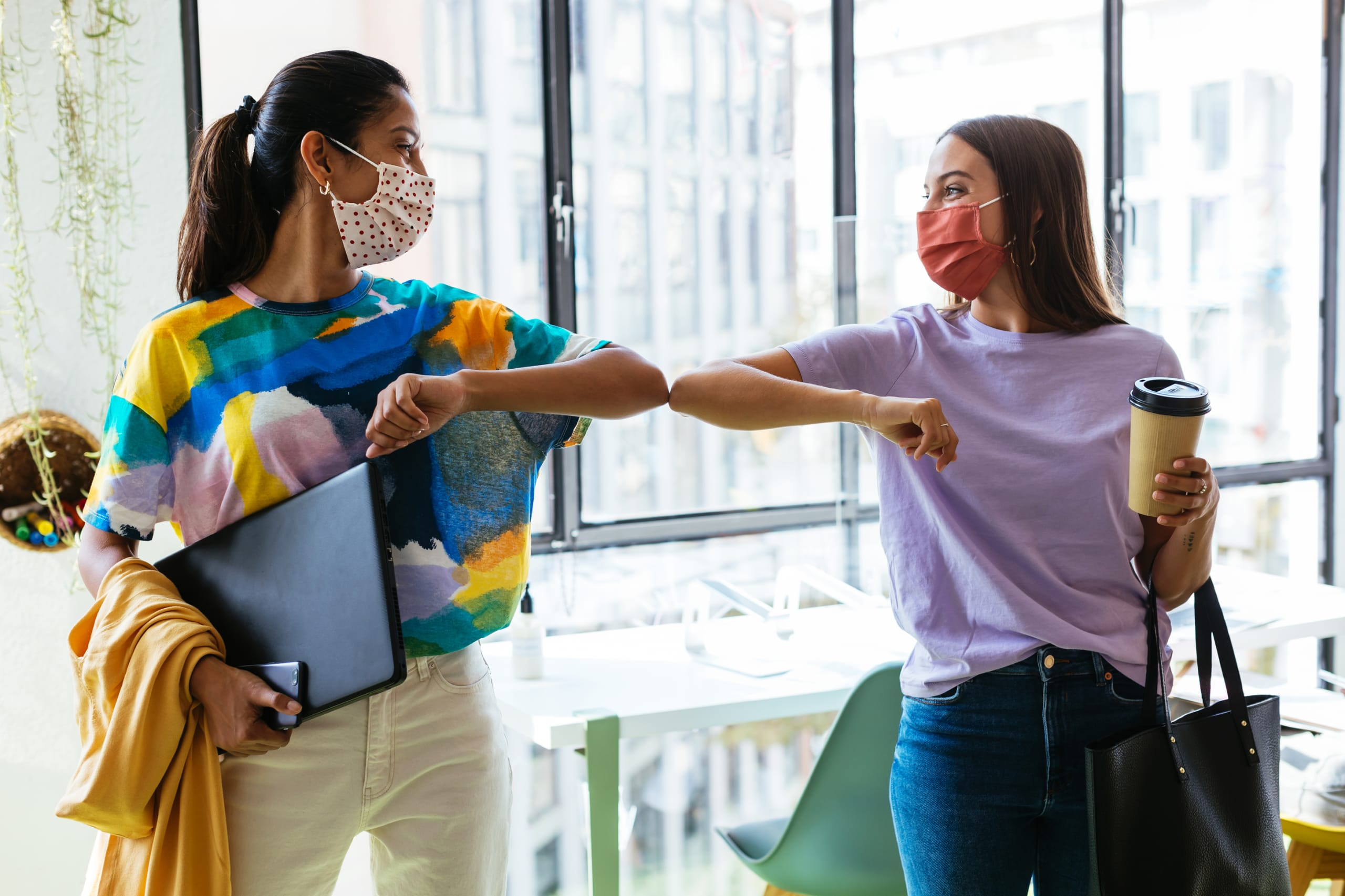 Female students greets each other during pandemic