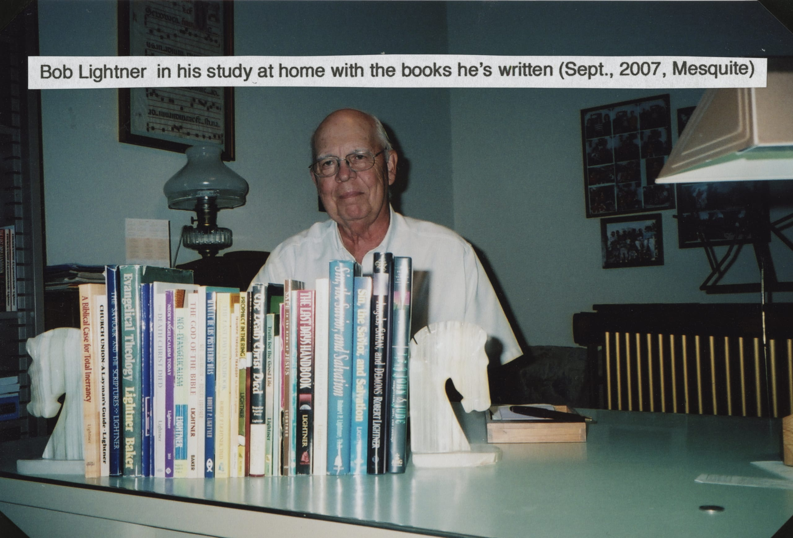 Dr. Lightner seated at a desk with copies of books he has written