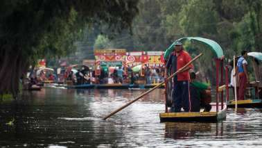 A man operates a trajinera boat at Xochimilco, Mexico.