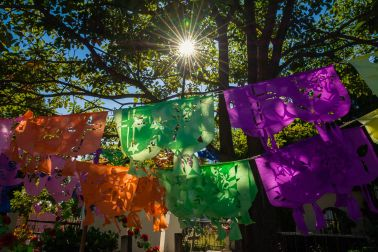 Hand-cut papel picado hangs above a grave in the Ajijic cemetery on the Day of the Dead.