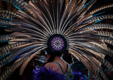 An Aztec dancer wears a large copili headdress made from peacock and turkey feathers during the Fiesta of the Virgin of the Rosary. The Virgin of the Rosary is the town