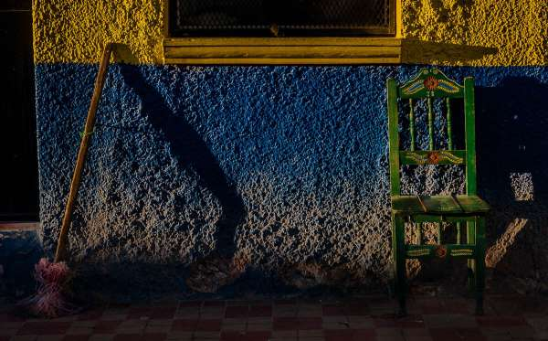 A chair and broom against a wall in the setting sun.