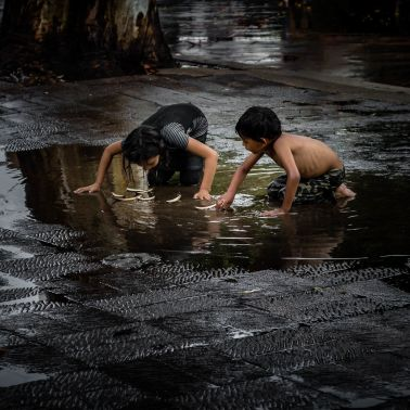 A brother and sister improvise and play in a puddle with boats they made out of fallen leaves after a brief afternoon thunderstorm hit the plaza in Ajijic, Mexico. One of the qualities that separates many kids who live in a place like the United States from, say, a place like Mexico is the ability, and at times the necessity, of creating games out of practical everyday items or found objects, such as pesos, rocks or these leaf boats, as shown in the photo.
