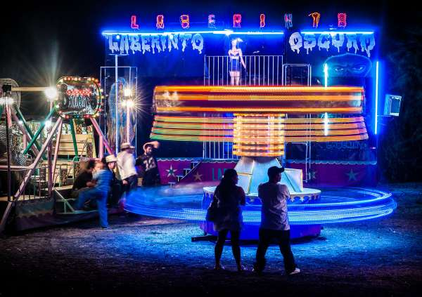 Parents wait for their child to finish a ride on one of the juegos mecánicos set up by a traveling carnival visiting Ajijic.
